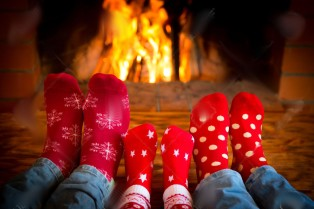 47423034-Family-relaxing-at-home-Feet-in-Christmas-socks-near-fireplace-Winter-holiday-concept-Stock-Photo